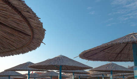 Reed beach umbrellas against blue clear sky Foto de archivo