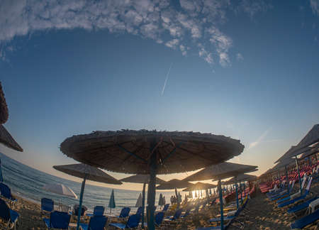 sunset beach with umbrellas and sunbeds without tourists