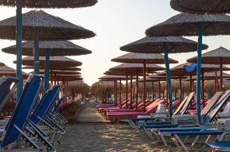 Beach with umbrellas and sunbeds without tourists Foto de archivo