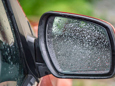 Closeup of car side rear view mirror with rain drops Imagens