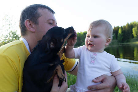 the Father and happy daughter play with dog