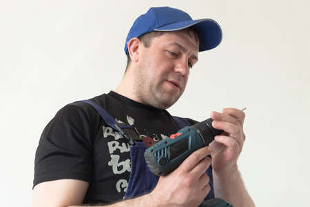 A professional carpenter with an electric drill in his hands.
