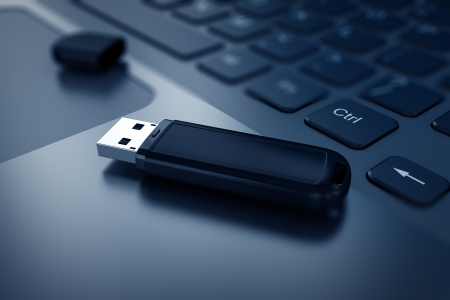 Modern USB Flash drive on laptop keyboard Stock Photo