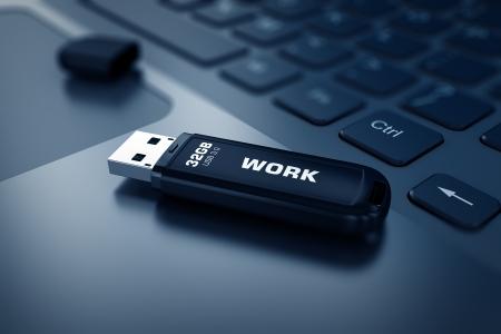 usb storage device: Modern USB Flash drive on laptop keyboard Stock Photo