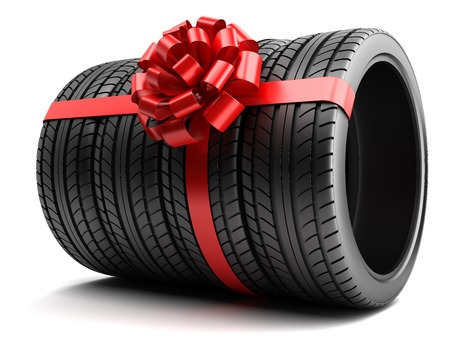 tire fitting: Gift set of tires wrapped ribbon and bow isolated Stock Photo