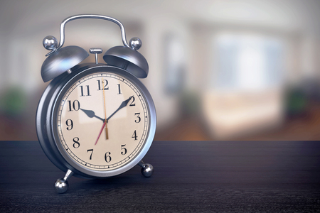 bedside: Retro alarm clock on bedside table in bedroom