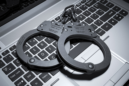 Handcuffs on laptop keyboard. Copyright concept 3d