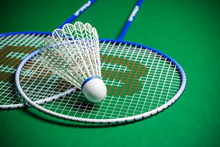 Badminton rackets and shuttlecock on green ground closeup shot. 3D render