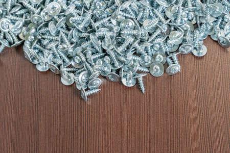 steel screws on a brown table Standard-Bild