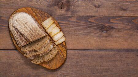 Smoked lard with bread on wooden background