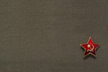 Military soviet star with hammer and sickle on fabric background