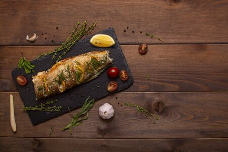 Baked fish with lemon on a wooden background