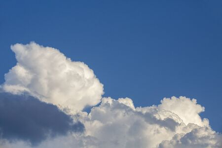 White contrasting clouds backlit by the sun on a blue summer sky. Background Banco de Imagens