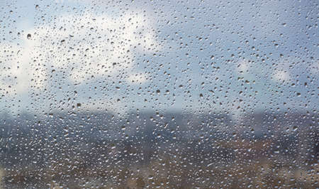 Drops on the window after the rain on the background of the city and the blue sky. Soft focus. Blurs.