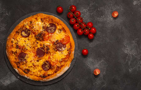 Delicious pepperoni pizza and ingredients on black concrete background. Top view of hot pepperoni pizza. With copy space for text. Flat lay. Banner. Zdjęcie Seryjne