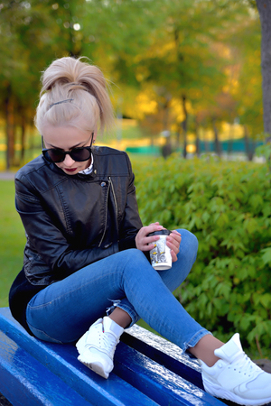 blonde in sunglasses, blue jeans and a black jacket sits on a blue bench with a glass of coffee