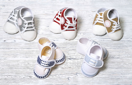 multi-colored childrens shoes on a white-gray non-uniform wooden background close-up Stockfoto