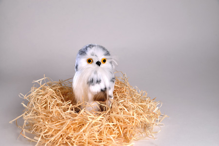 Toy eagle owl from a natural feather sits in a nest standing on a gray background