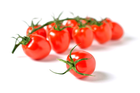 one cherry tomato on a background of cherry twig, white background close-up
