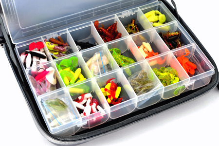 A box with a variety of silicone baits lies in a fishing bag, white background close-up