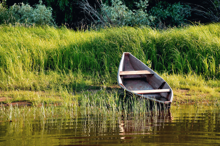 old wooden boat on the river bank or clouds close up against the background of green grass and bushes, reflections in the water Stock Photo