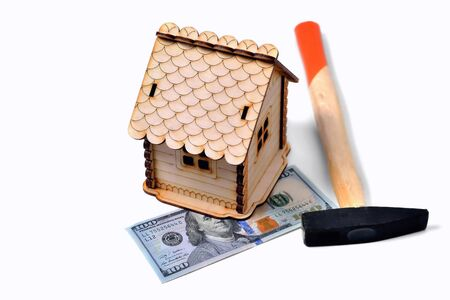 Wooden toy house, a banknote of 100 dollars and a hammer on a white background, isolate