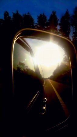 car mirror reflection of the morning sun in the mirror the terrain in the background close-up 版權商用圖片