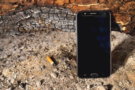 phone in a fire ash firewood dust side sunlight cigarette butt cigarette burnt log close-up