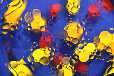 Background from multi-colored small balls of heterogeneous coloring, mainly blue, interspersed with red and yellow tones, texture, blur, close-up