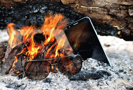 Sunglasses and telephone are burning in the bright flame of the fire, ash firewood close-up 스톡 콘텐츠