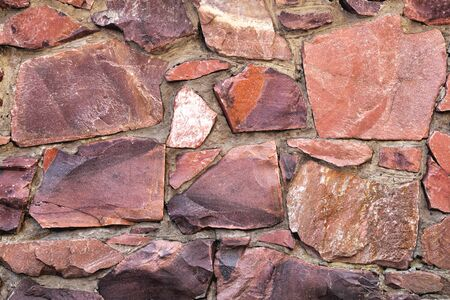 The wall of large raw granite stones of red color, background granite non-uniform Stock Photo