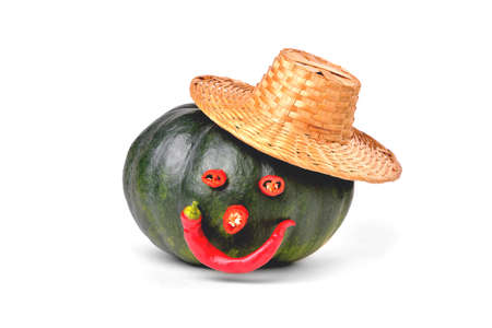 Natural green pumpkin, rustic straw hat, funny funny face of hot pepper, on a white background close-up