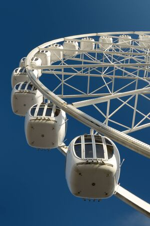 the height of a rim: A fragment of the attraction, the Ferris wheel on the background of blue sky. Stock Photo