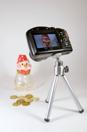 acts: A small camera mounted on a tripod.The role models acts as a piggy Bank.
