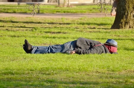 lay off: The man was tired.He took off his shoes and lay down on the grass to sleep. Stock Photo