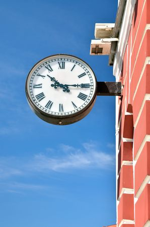 show time: The City Of St. Petersburg.The clock hanging on the wall of the building and passers-by show time. Stock Photo