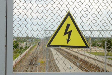weighs: On the grid of the fence weighs sign.It warns of high voltage electricity. Stock Photo