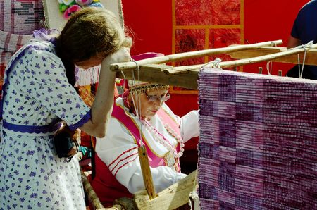 04.07.2015.Russia.Saint-Petersburg.Festival of the masters.A woman weaves a carpet as they did in the old days. Editorial