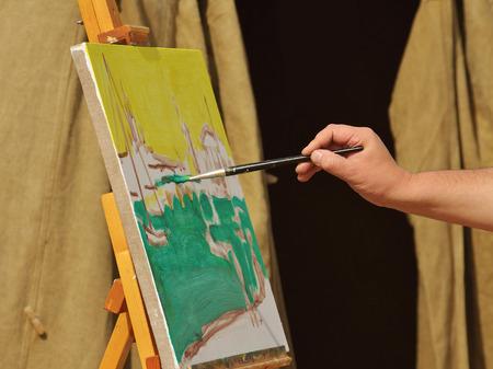 artist's canvas: The artist paints on canvas a beautiful cityscape. Stock Photo