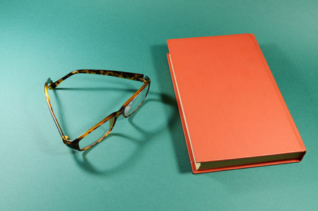 lies: On the table lies a book and glasses for vision.