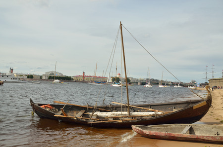 drooping: Wooden boat with drooping sails,moored to the shore. Stock Photo