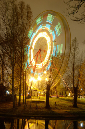 rotates: The Ferris wheel rotates and glows brightly at night. Stock Photo