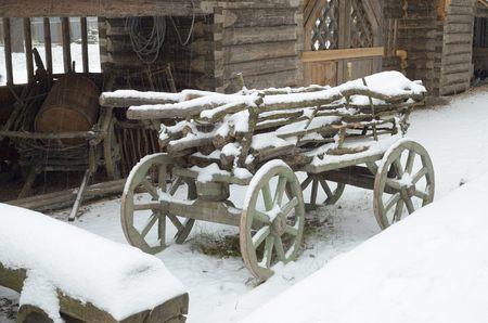 carreta madera: Carro de madera está en el patio cubierto de nieve.