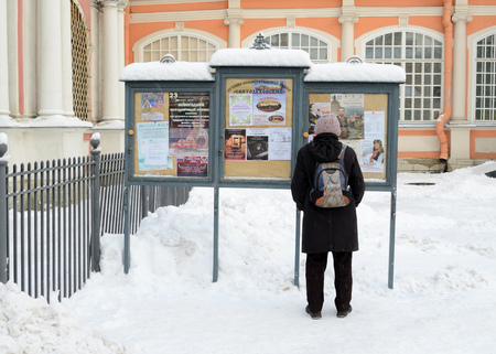 news stand: 03.12.2016.Russia.Saint-Petersburg.A man reads news on the stand in the monastery. Editorial