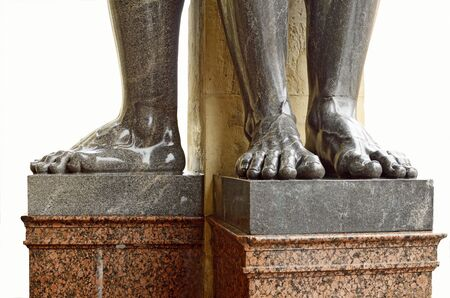 A fragment of stone sculpture.We see the feet of granite.