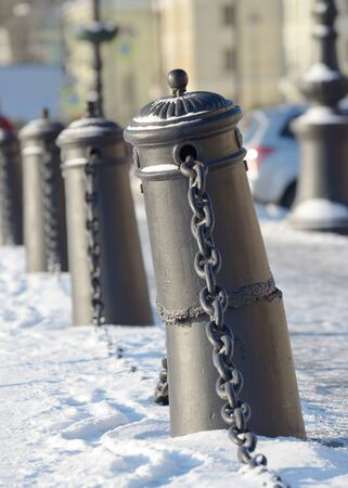 Protective pillars with chain exhibited along the city waterfront.
