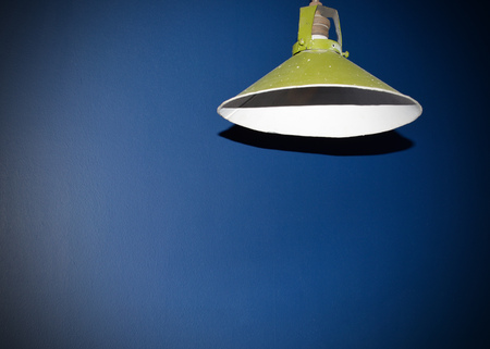 Round Green Lampshade hanging on the ceiling in the room. Stock Photo