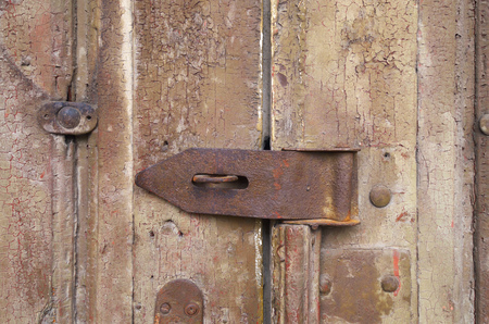 Wooden door with steel eyelets for a lock. Imagens - 82869492
