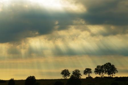 日没時の太陽の光。ライトは、雲の切れ間から中断します。 写真素材