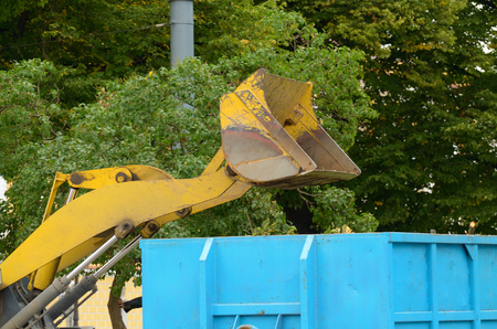 On the streets, cut off dry branches on trees.The tractor dumps them in the trash. Stockfoto